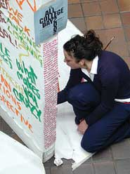 A student paints on the ACD mural