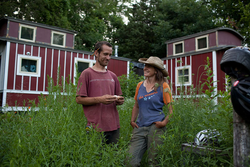 """Miriam Latzer '97 and boyfriend Justin in front of their caboose-shaped residence at Loose Caboose Farm in Clermont, New York. """"The caboose is loose because it has no breaks,"""" Latzer says of her growing business."""