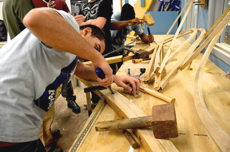 A participant attends to fine details on the boat, which will be displayed at the Mystic Seaport Museum.