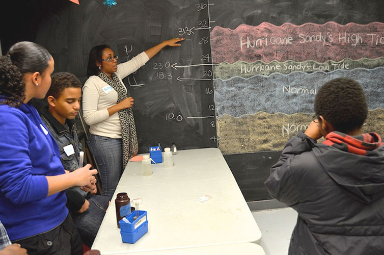 During Family Night, a volunteer explains the effect of Hurricane Sandy on the New York City waterway.